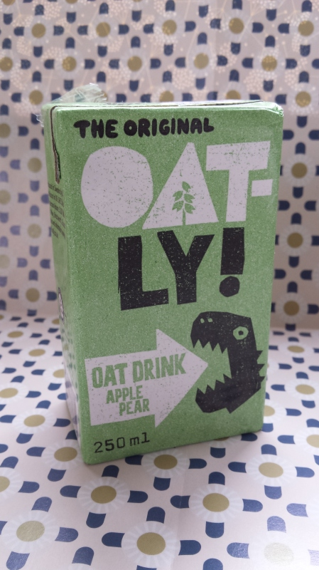 A carton of Oatly Apple & Pear drink against a patterned background
