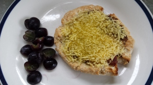 A home made pizza on a plate with some grapes.