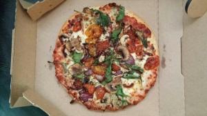 A four veggie pizza in an open takeaway box.