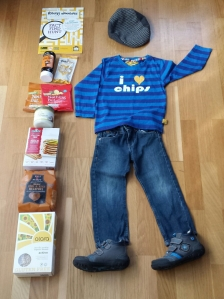 A stack of free from foods next to a small boy's clothes laid out as if he is wearing them.