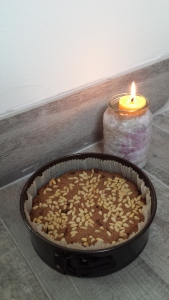 A cake in a tin with a candle.