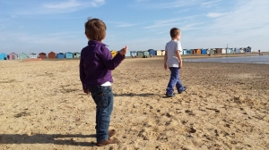 Two young boys are on a beach. They are facing away from the camera and are a bit over dressed.