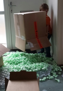 A small boy has turned over a large cardboard box, and there are packing peanuts everywhere.