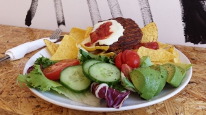 A Messy Mexican burger with tortilla chips and salad