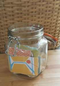 A kilner jar filled with colourful, illustrated cards.