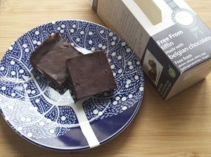 Two slices of chocolate tiffin on a plate next to the packaging.