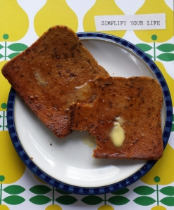 Two slices of Amisa rice bread toasted and buttered on a plate.  One slice has a bite out of it.